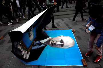 Tourists pick up a portrait of Russian President Vladimir Putin painted by Russian artist and former mayor of Arkhangelsk Alexander Donskoy at Istiklal Street in Istanbul