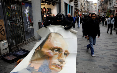 Russian artist and former mayor of Arkhangelsk Alexander Donskoy picks up a portrait of Russian President Vladimir Putin at Istiklal Street in Istanbul