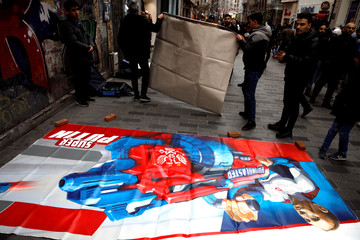 Officials pick up portraits of Russian President Vladimir Putin painted by Russian artist and former mayor of Arkhangelsk Alexander Donskoy at Istiklal Street in Istanbul