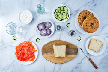 Marble table with ingredients for making bagel or sandwich for lunch