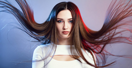 Wall Mural - portrait of girl with long hair flying in air on studio background, young woman looking straight confidently , fashion model,confrontation of two sides of the personality red and blue