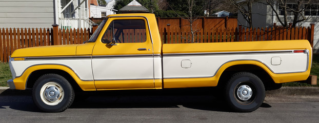Vintage two tone white and yellow long bed pickup truck parked on neighborhood street.
