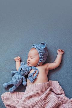 Cute newborn baby girl sleeping with teddy bear on gray blanket.