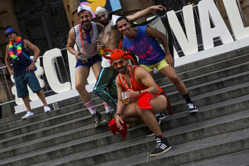 """Revellers pose for pictures next to sign that reads """"carnival"""" in Portuguese, while they take part in the annual block party known as """"Casa Comigo"""" (Marry Me), during carnival festivities in Sao Paulo"""
