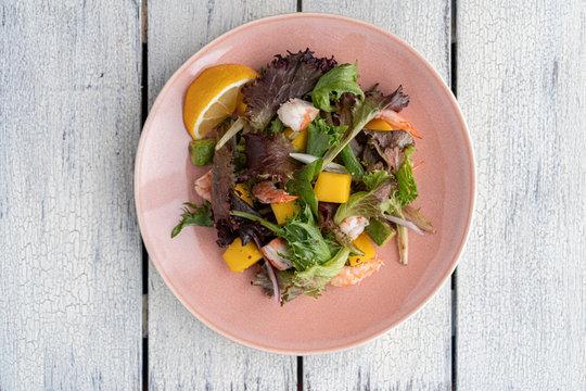 Homemade green salad with spring mix, mango, avocado and shrimps.