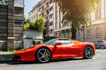 STRASBOURG, FRANCE - MAY 28, 2018: City parking with expensive luxury Ferrari car red color parked on street in sunlight