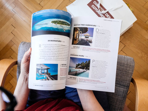 PARIS, FRANCE - JUL 1, 2018: French woman reading on wooden office table travel catalogue with luxury Maldives destination - view from above