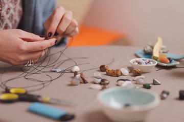 Woman hands making handmade gemstone jewelry, home workshop. Woman artisan creates jewelry. Art, hobby, handcraft concept