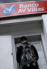 A man uses an ATM at a Banco AV Bank in Bogota