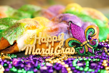 Happy Mardi Gras text in gold glitter and a king cake with yellow, green, and purple sprinkles surrounded by Mardi Gras beads and a glittering fleur de lis.