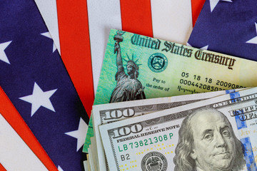 Stimulus economic tax return check and US 100 dollar bills currency with US flag