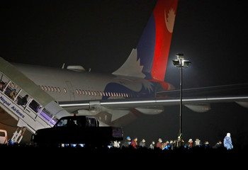 Nepalese nationals who were in the coronavirus-stricken Chinese city of Wuhan walk out from Nepal Airlines plane carrying 175 Nepalese nationals, while they were sent to be quarantine, at Tribhuvan International Airport in Kathmandu