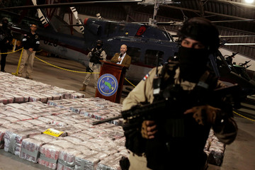 Police officer is seen in front of packages containing cocaine seized during an operation in the Caribbean, as Michael Soto, Minister of Public Security, speaks to the media in Alajuela