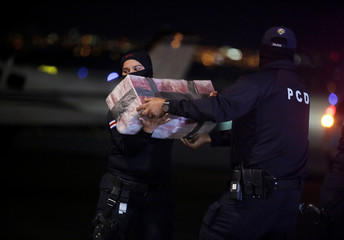 Police officers carry packages containing cocaine seized during an operation in the Caribbean, at the air base of the Ministry of Security in Alajuela