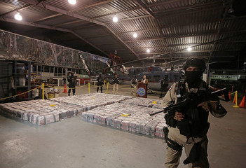 A police officer is seen in front of packages containing cocaine seized during an operation in the Caribbean, as Michael Soto, Minister of Public Security, speaks to the media at the air base of the Ministry of Security in Alajuela