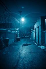 Fototapete - Dark and eerie urban city alley at nightin the winter