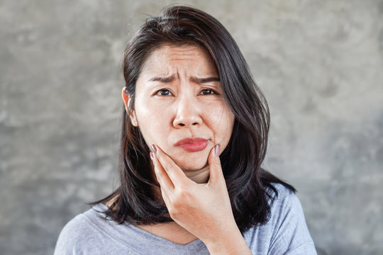 depressed Asian woman having problem with Bell's Palsy/Facial Palsy, hand holding her face