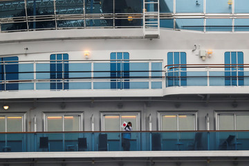 A passenger wearing a protective face mask holds a Japanese national flag while standing on the cruise ship Diamond Princess in Yokohama
