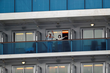 Passengers wave from the cruise ship Diamond Princess in Yokohama