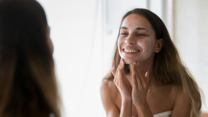 Smiling young woman scrub face with beauty mask Fotomurales