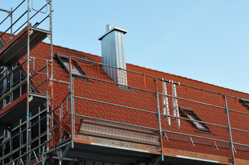 scaffold and red safety net at a roof