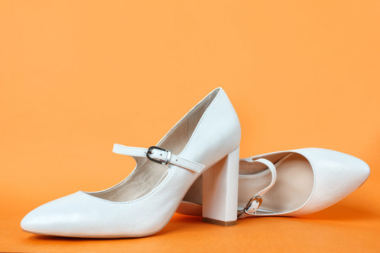 White high heel women's shoes on a orange background. Side view, close up. Stylish trendy shoes for the spring and summer season. Feminine fashion concept. Legendary Mary Jane Shoes.