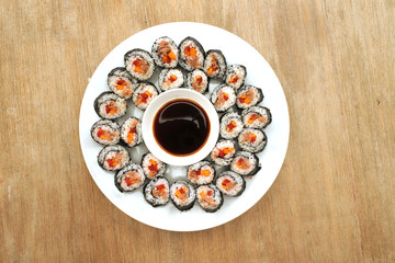 Many sushi slices served on white plate with soy sauce