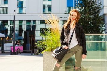 Casual girl with handbag on city street