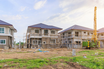 New house building at residential estate construction site with clouds and blue sky