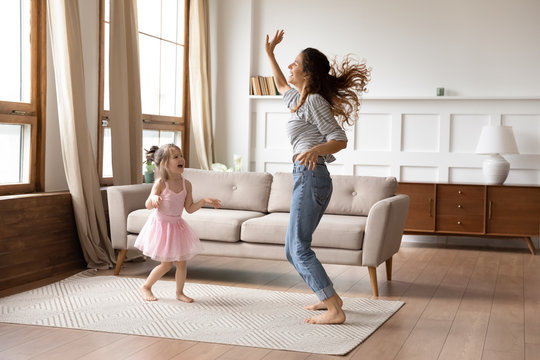 Crazy energetic family of two dancing in living room.