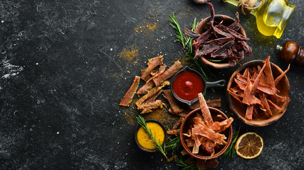 Jerky. Dried meat slices with spices and herbs. Snacks for beer On a black stone background. Top view.
