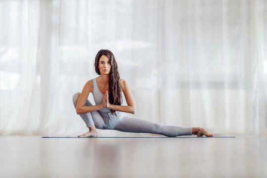 Young attractive fit slim girl with long hair in Side Lunge position. She is looking at camera. Yoga studio interior.