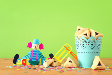 Purim celebration concept (jewish carnival holiday) over wooden table and green background