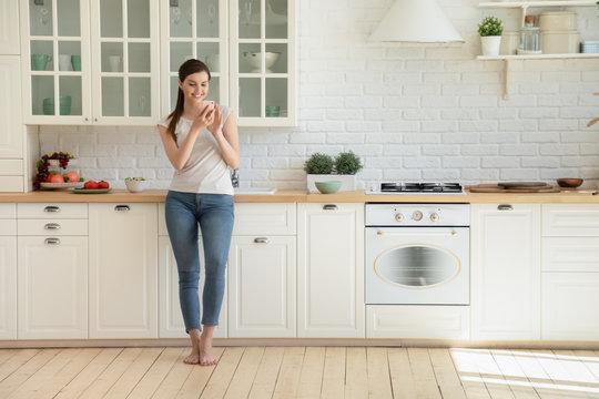 Millennial girl using cellphone in modern home kitchen
