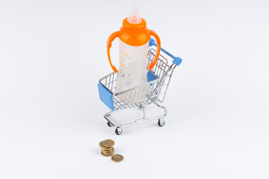 Shopping cart with baby bottle and moneys on white background