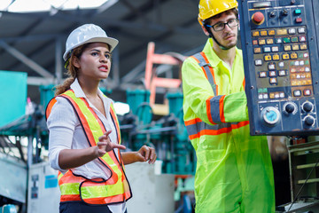 Male and Female Industrial Engineers in Hard Hats Discuss talking. Female industrial engineer standing in a heavy industrial factory behind she talking with engineer setup the machine,