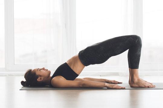 Relaxed girl streching body in bridge pose