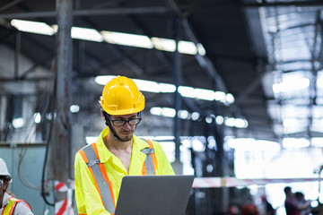 Men industrial engineer in uniform and wearing a Yellow helmet while standing in a heavy industrial factory behind he looking New Project while Using Laptop.