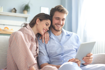 Young couple in pajamas watching media content online in a tablet sitting on a sofa in the living room.