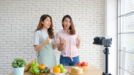 Two young asian food blogger recording cooking tutorial, Asia girls vlogger thumb up and looking at camera while streaming live on social media, Female food blog influencer broadcast healthy food