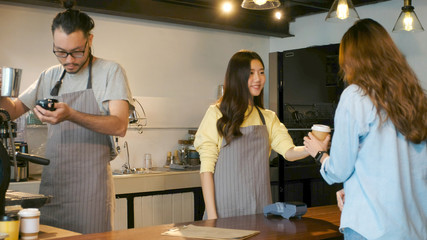 Young asian barista woman serving take out coffee cup to customer at counter in coffee shop cafe background, asia small business owner, start up