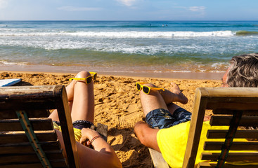 couple of adults on wooden sun beds near the sandy beach enjoy rest and look at the ocean. Sri Lanka, Asia.