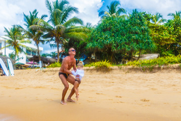Father throwing his daughter in air at tropical beach