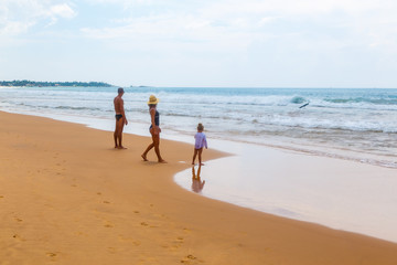 family with little dother holding hands and walking on sand tropical beach waves and people in the background