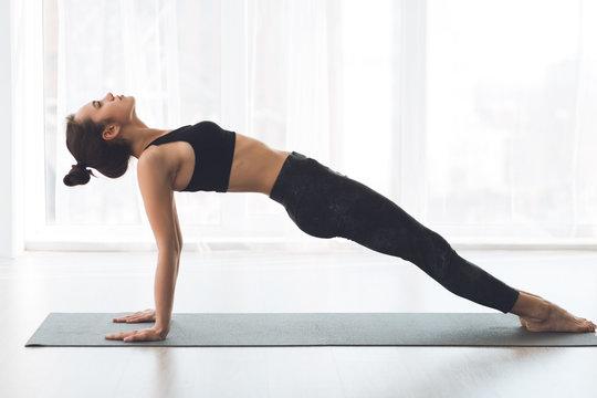 Woman doing upward plank exercise at modern studio