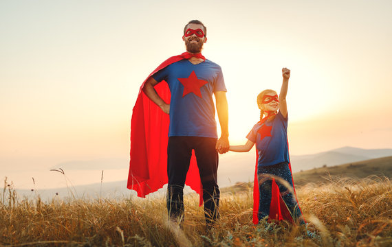 concept of father's day. dad and child daughter in hero superhero costume at sunset  .