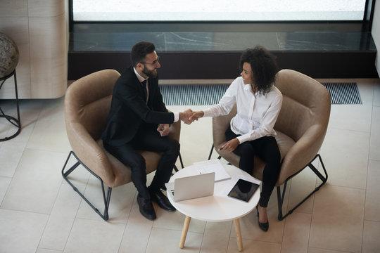 Arabian businessman african businesswoman shaking hands sit on armchairs indoors