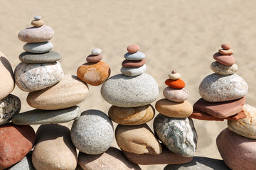 Photo sur Plexiglas Zen pierres a sable Lots of balanced, colorful pebbles on a beach on the background of the sand.