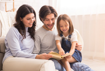 Parents teaching their little daughter how to read at home
