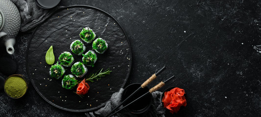 Sushi rolls with seafood and Chuka salad. Green sushi. Top view. Free space for your text.